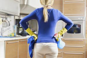 Kvinne på kjøkken med gummihansker og rengjøringsutstyr. Grundig flyttevask av kjøkken og resten av leiligheten utført av våre dyktige renholdere.
